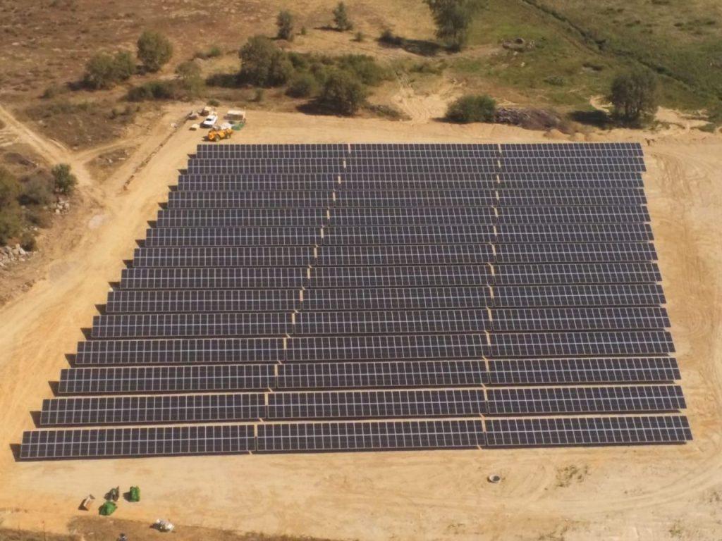 campo com paineis fotovoltaicos, arvores e carros